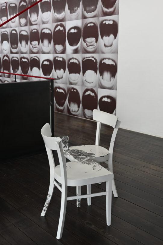 Au premier plan : Nick Mauss, Printed, 2010, impressions sur chaises en bois, 84 x 115 x 86 cm, Frac Champagne-Ardenne © Nick Mauss. Au second plan : Graciela Sacco, Bocanada, 2015, 12 affiches couleurs, 70 x 50 cm, 49 Nord 6 Est – Frac Lorraine © M. & C. Garavelli Sacco.